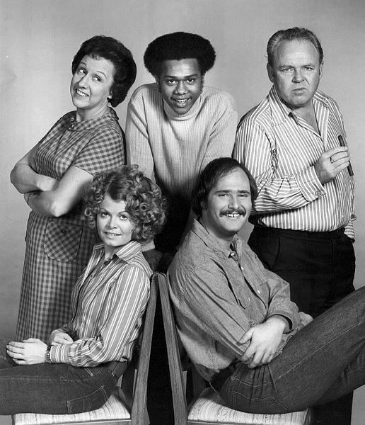 Photo of the cast of the television program All In the Family. Standing, from left: Jean Stapleton (Edith Bunker), Mike Evans (Lionel Jefferson), Carroll O'Connor (Archie Bunker). Seated: Sally Struthers (Gloria Bunker Stivic) and Rob Reiner (Mike Stivic).
